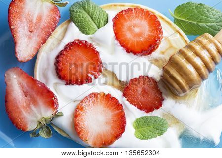 Pancake with strawberries honey and mint on a blue surface