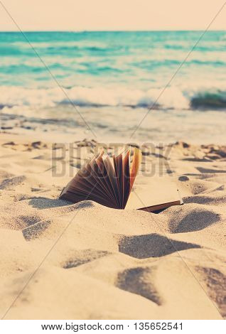 An open book laying on a sandy beach at sunset. Toned.