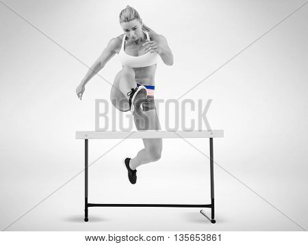 Female athlete jumping on white background