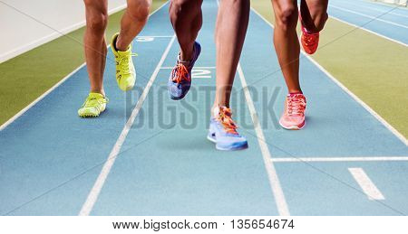 Close up of sportsman legs running against view of a running track