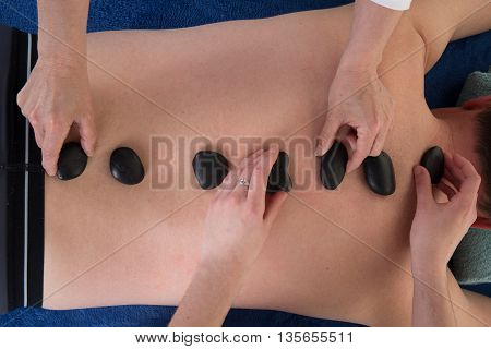 Male Having Hot Stones On Her Back By Two Woman