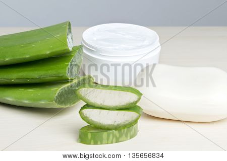 Fresh aloe vera leaves with soap, closeup