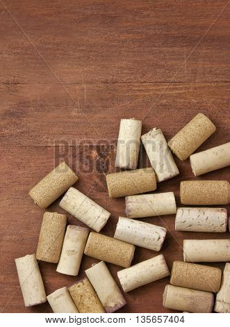 Many wine corks shot from above on a dark brown wooden background texture with a place for text