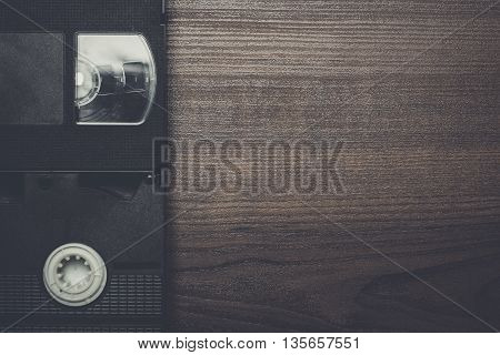 old retro video tapes over brown wooden background