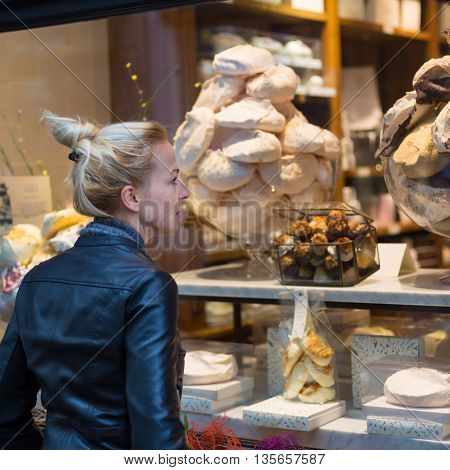 Lady window shopping in front of sinfully expensive chocolate boutique store dispaly window. Customer woman in shopping street, looking at window, outdoor.