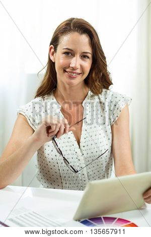 Portrait of businesswoman holding digital tablet in office