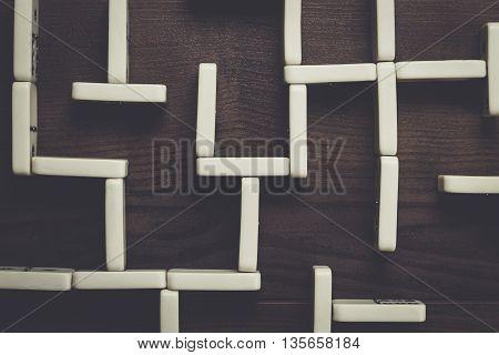 domino pieces maze on dark brown wooden background