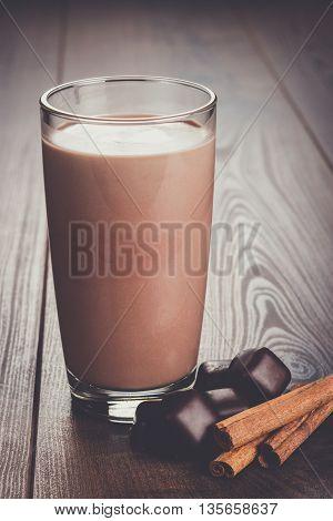glass of chocolate milkshake and cinnamon on the table