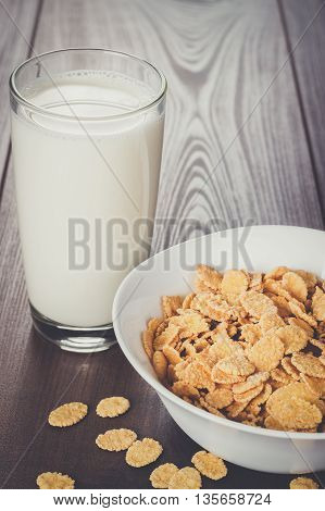 glass of milk and bowl with cornflakes on the table