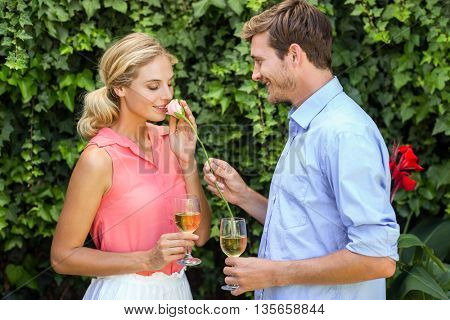 Young man giving flower to woman while holding wineglasses at front yard