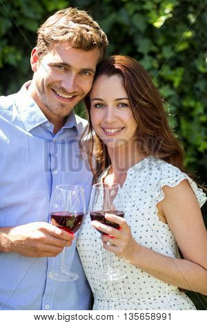 Portrait of romantic couple holding wineglasses at front yard