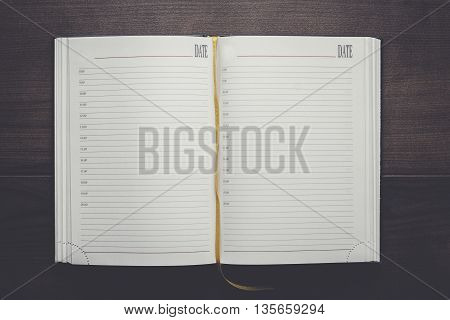 opened notebook on the brown wooden table