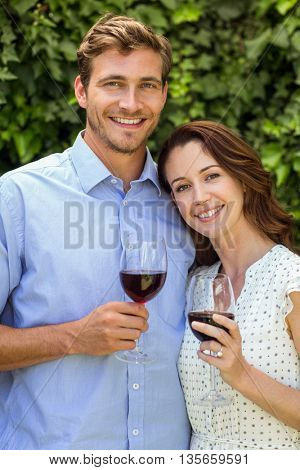 Happy smiling couple holding wineglasses at front yard