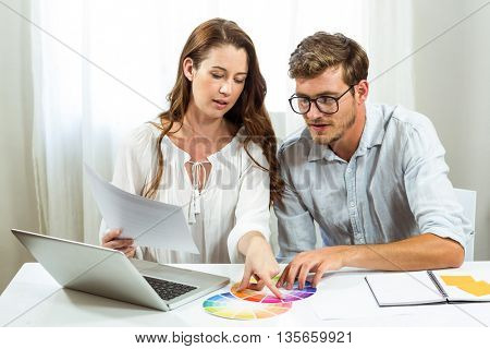 Male and female collegues discussing colour samples at desk in creative office