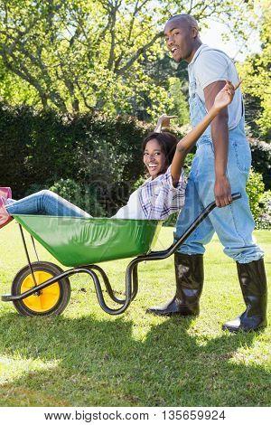 Portrait of young man giving woman a ride in the wheelbarrow in their garden