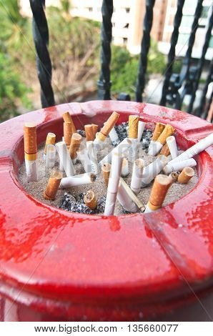 red plastic ashtray containing cigarette butt and ashes