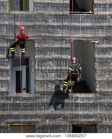 Bold And Daring Climbers Of Firefighters Climbing A Wall