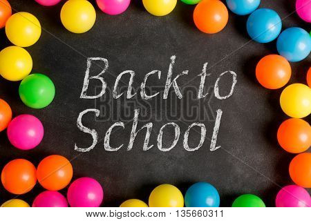 Chalkboard with inscription back to school and colorfull plastic balls