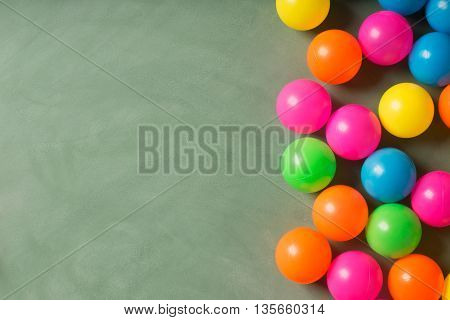 Green chalkboard with copy space and colorfull plastic balls on the board