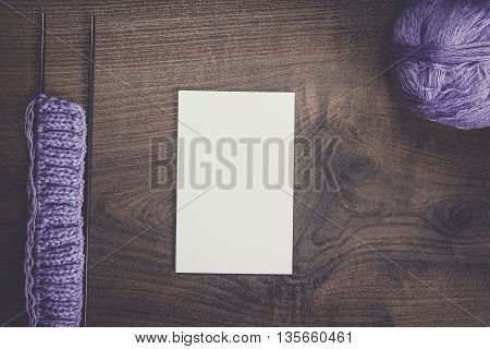 knitting needles and blank notebook on the table background