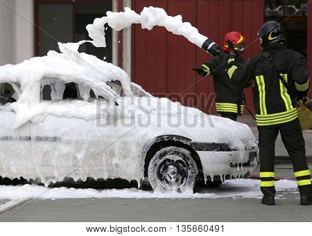 Firefighters During Exercise To Extinguish A Fire In A Car