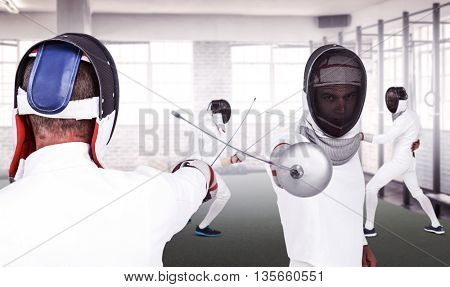Man wearing fencing suit practicing with sword against gym