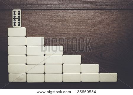 leadership concept. domino pieces forming stair over wooden background