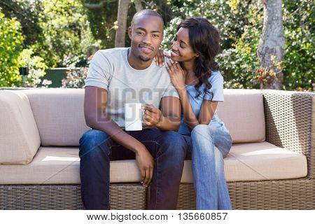 Young couple relaxing on the sofa and holding coffee mug in the park