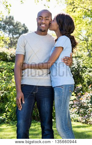 Young woman kissing man on his cheeks in the park