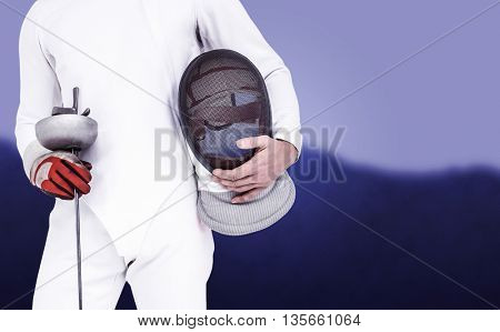 Swordsman holding fencing mask and sword against blurred mountains