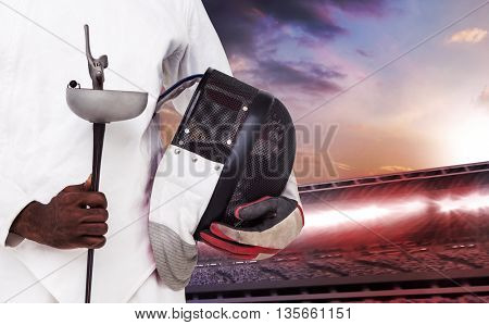 Mid-section of man standing with fencing mask and sword against composite image of stadium with cloudy sky