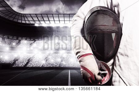 Mid-section of man standing with fencing mask against sports arena