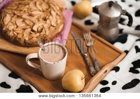 Cup of coffee and apple pie staying on wooden tray in bed close up. Tasty breakfast. Good morning.