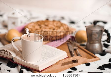 Cup of coffee staying on open book apple pie on wooden tray closeup. Good morning. Selective focus.