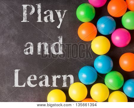 Black chalkboard with play and learn inscription and colorful plastic balls