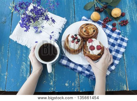 hands holding a blue cup.Breakfast with biscuits and fresh berries.