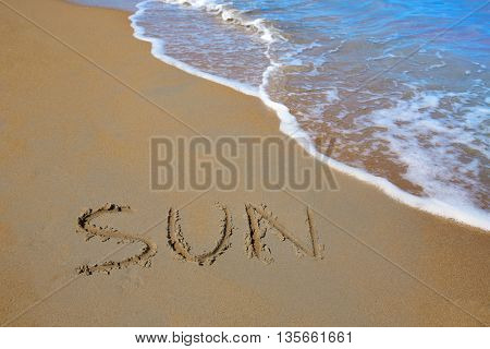 Sun spell written work in sand of a beach in vacation