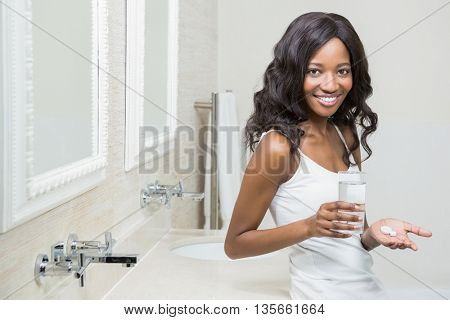 Portrait of beautiful woman holding pill and glass of water in the bathroom
