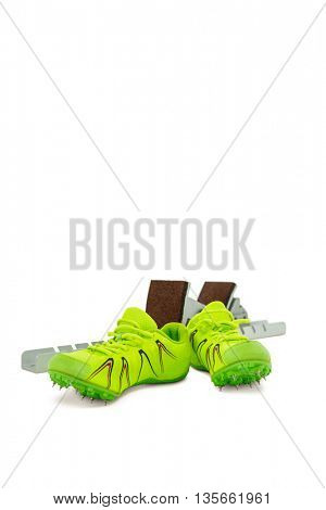 Trainer shoes and starting block on isolated white background
