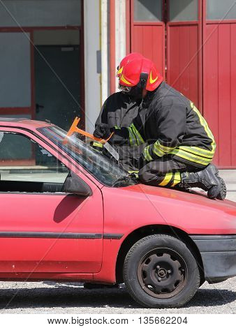 Fireman Cuts The Windshield  Of Car With A Hacksaw