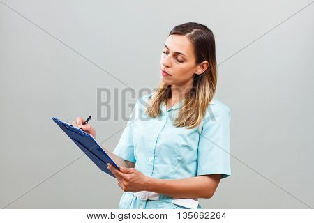 Photo of beautiful serious nurse writing notes.
