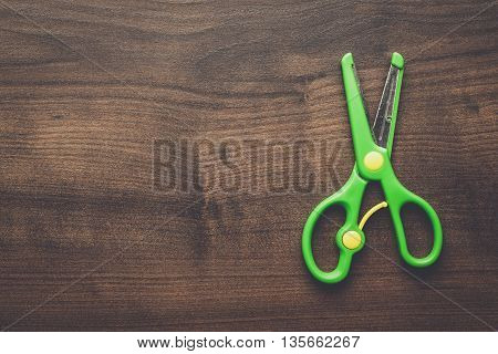 children's scissors on the brown wooden table