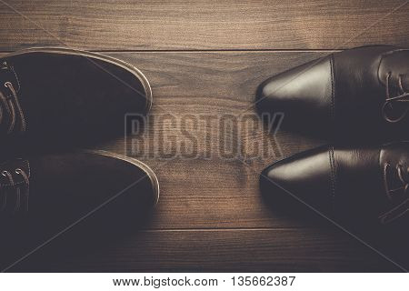 two pairs of brown shoes on the wooden table