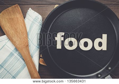 big frying pan on the table with word food