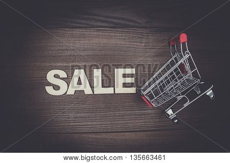 sale concept on the wooden background. shopping trolley