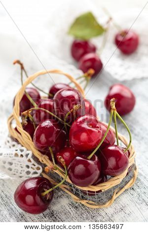 Ripe cherries in small basket. On white wooden table.