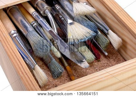 Old wooden box with paint brushes on white backgound