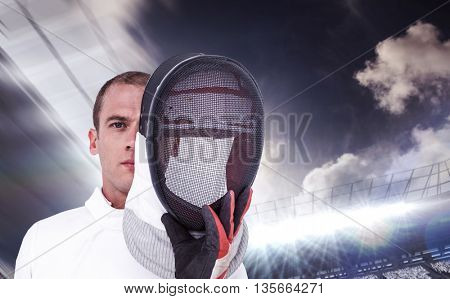 Swordsman holding fencing mask against football stadium with fans in white