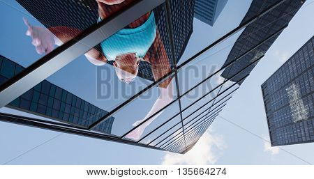 Low angle female athlete jumping against skyscraper