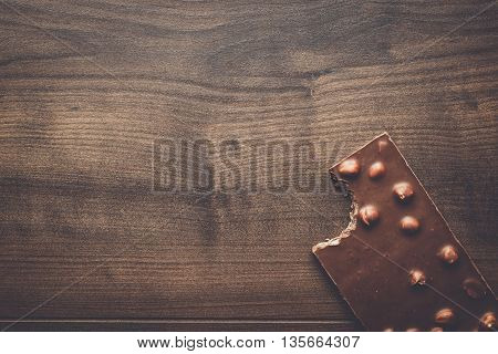 nibbled chocolate bar with whole hazelnuts on wooden table